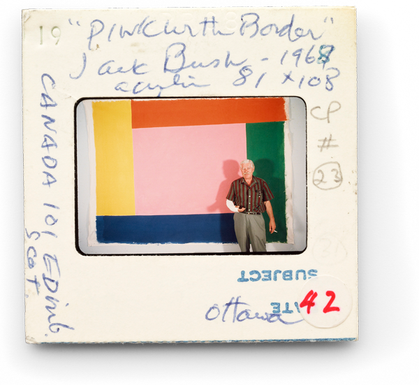 "Jack Bush standing in front of his painting ""Pink With Border"" (1967)"